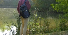 Man in Glasses With Backpack Comes to Lake Bank Put Down His Backpack Sits and Stock Footage
