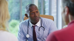 4K Friendly doctor talking to a couple in his office. - stock footage