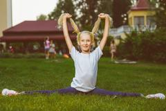 smiling happy little girl doing split and holding itself for pigtails - stock photo
