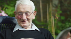 4K Portrait of elderly man sitting alone reading newspaper in the garden Stock Footage