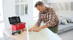 Middle-aged man at home assembling furniture parts Stock Footage
