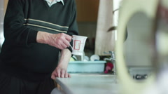 4K Portrait of elderly man alone, having a hot drink in his kitchen.  Stock Footage