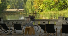 Stock Video Footage of Terrace Opposite The Lake Black Deckchairs And Table With Teapot And Cup On The