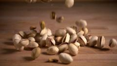 Pistachio nuts falling onto kitchen counter, slow motion Stock Footage