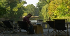Man Sits In The Deckchair On The Terrace Opposite The Lake He works On Computer Stock Footage