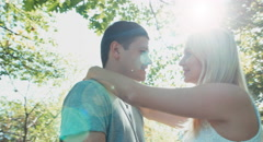 Young adults looking eyes to eyes are in the park. Lens flare Stock Footage