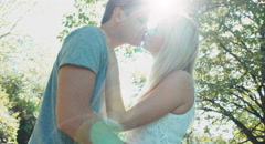 Young adults looking eyes to eyes and kissing in the park. Lens flare - stock footage