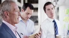 4K Attractive male business team brainstorming for ideas with sticky notes - stock footage