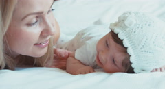 Closeup portrait mother playing with newborn child and looking at camera - stock footage