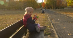 Little Blonde Girl in Beret Red Scarf And Jacket is Holding the Bouquet Made of Stock Footage
