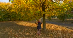 Little Blonde Girl in Beret Red Scarf And Jacket is Pulling the Tree Branch to Stock Footage