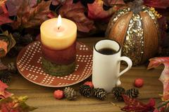 Coffee, Lit Candle and Pumpkin Decor - stock photo