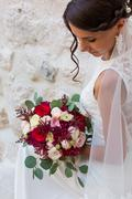 Beautiful bride outdoors with a bouquet - stock photo