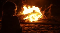 Silhouette of child in front of the bonfire on beach party in the dark. Vietnam - stock footage