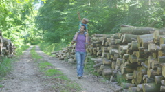 4K Happy father & son spending time outdoors & walking along forest path - stock footage