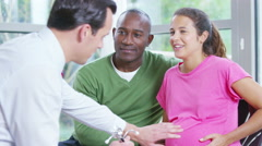 4K Friendly doctor talking to couple who are expecting a baby. - stock footage