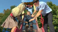Parents with children ride toddler slides - stock footage