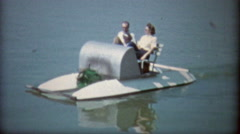 1968: Family packed into a paddleboat on a pond. Stock Footage