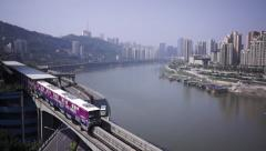 Light rail lines and overpass traffic along the Yangtze river, Chongqing Stock Footage