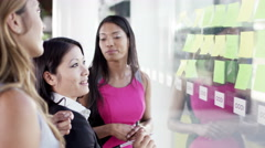 4K Attractive female business team brainstorming for ideas with sticky notes - stock footage