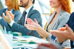 Row of colleagues applauding to speaker at seminar Stock Photos