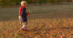 Little Girl With Blonde Braid in Beret and Red Scarf is Walking by Dry Grass in Stock Footage