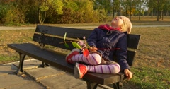 Girl With Bouquet Made Up of Leaves is Sitting on the Bench with Her Legs Stock Footage