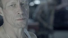Auto mechanic smoking cigarette in garage - stock footage