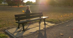 Girl With Bouquet Made Up of Leaves is Walking around the Bench in Park Sits - stock footage