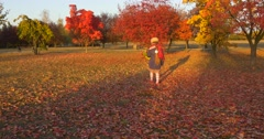 Little Girl in Beret And Blue Jacket is Walking by Park Zoom In Girl's Back Stock Footage