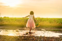 Cute little girl playing in puddle - stock photo