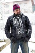 wary man standing in a snowy garden - stock photo