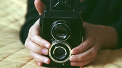 Woman using an old vintage, retro camera touching lens Stock Footage