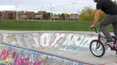 BMXer drops into ramp and airs as camera smoothly follows - stock footage