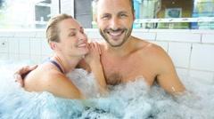 Couple enjoying hot tub bath in spa center Arkistovideo