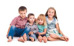 four cute children sitting on the floor - stock photo