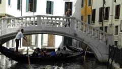 VENICE, ITALY - AUGUST 2012: Gondolier sails gondola under a bridge Stock Footage