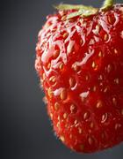 Cropped macro view of whole strawberry with drops of water on dark grey backg - stock photo