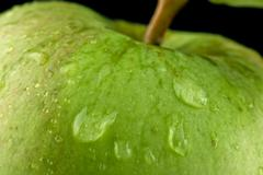 x-default Close-up shot of green apple with drops of water on black backgroun - stock photo