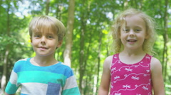 4K Portrait of happy little boy & girl in the woods, waving to camera Stock Footage