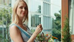 Portrait pregnant woman with blonde hair eating salad and standing - stock footage