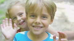 4K Portrait of happy little boy & girl in the woods, pulling faces Stock Footage