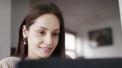 4K Young woman cheerfully typing on her laptop at home, in slow motion Stock Footage