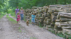 4K Happy family spending time outdoors & walking pet puppy along forest path Stock Footage