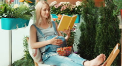 Pregnant woman with blonde hair reading a book in the garden and eating straw - stock footage