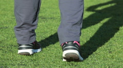 Runners standing on the green grass field and warming up legs for competition Stock Footage