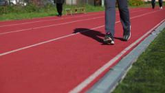 Close up view at female legs finishing run over rubber surface on stadium lane - stock footage
