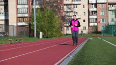 Front view of Caucasian sportswoman running at the stadium lane, morning workout Stock Footage