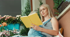 Pregnant woman with blonde hair pats belly and reading a book in the garden - stock footage