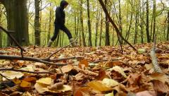 Woman kicks leaves as she walks in woods - stock footage